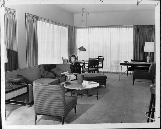 Woman sitting in a living room of a hotel or apartment reading a magazine near the couch