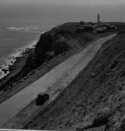 A lighthouse with a car approaching on a dirt road