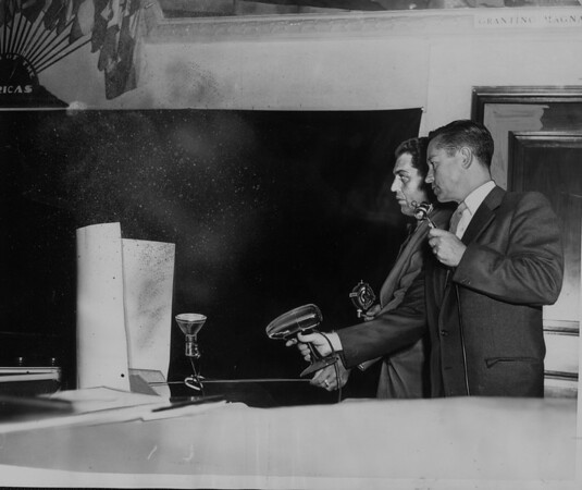 Engineer Leo Calstrom (left) and Howard Clark demonstrate at a hearing how wind would blow dust from a proposed diatomaceous earth mine in Palos Verdes