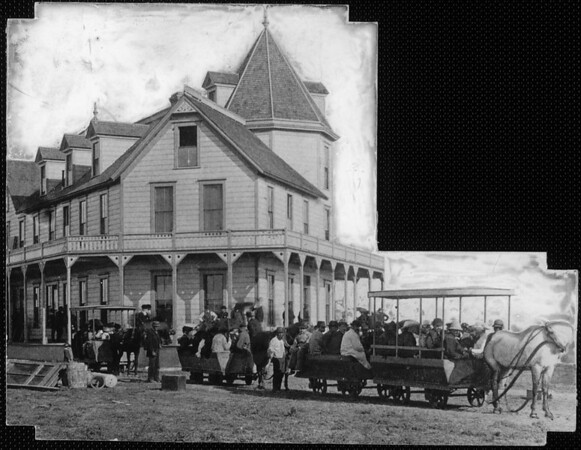 Two horse-drawn trolley cars loaded with passengers in front of a 2-story Victorian wood siding building with numerous gables and an octagonal tower