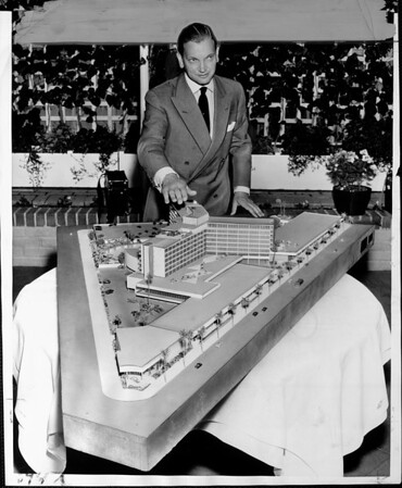 Man in a suit holding his hand over an architect's model of the Beverly Hilton hotel