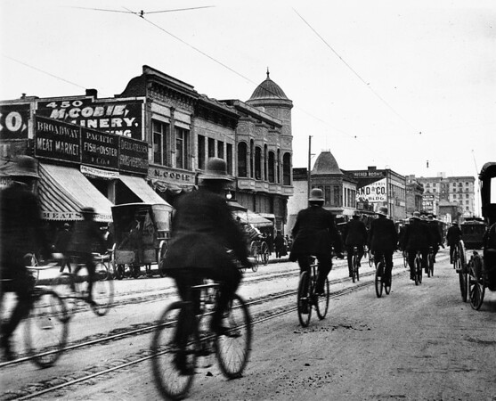 Uniformed men riding bicycles near the corner of Fourth Street and Broadway