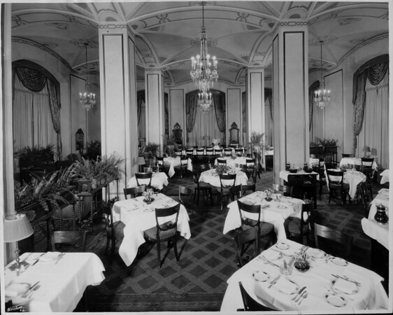 Empty dining room in a hotel? with table set with white linen, silverware, plates and napkins