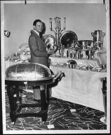 Man in a suit standing beside a large collection of silver table service (silverware, plates, trays, tureens, candelabra)