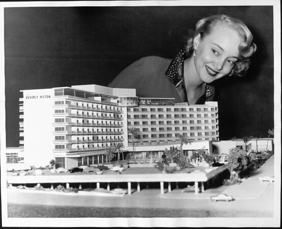 Blonde woman looking down on an architect's model of the Beverly Hilton hotel