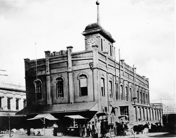A building with a clock on top which is surrounded by people with horses and buggies