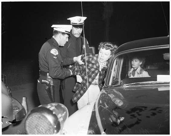 Drunk women taken from car with baby, 1953