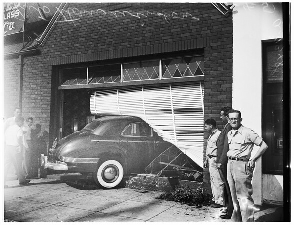 Auto through window of building, 1951