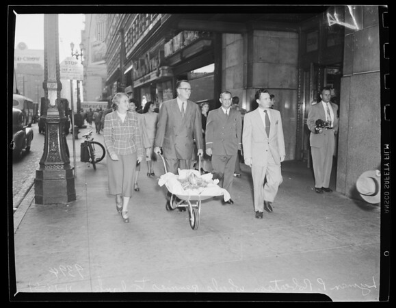Pennies hauled to bank in wheelbarrow by vice president and employee of Pacific Mutual, 1951