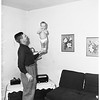 Baby stands on father's hand, 1951