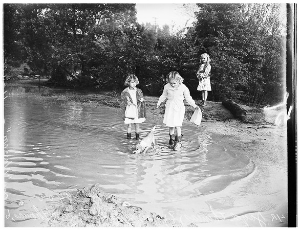 """Rainy weather ...Children wading through """"swimming pool"""" on way to Monterey Vista School to get to class after rains flooded portion of Toll Drive, 1951"""
