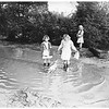 "Rainy weather ...Children wading through ""swimming pool"" on way to Monterey Vista School to get to class after rains flooded portion of Toll Drive, 1951"
