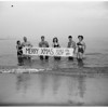 """Venice Beach enthusiasts swim in ocean with """"Merry Christmas"""" sign, 1951"""