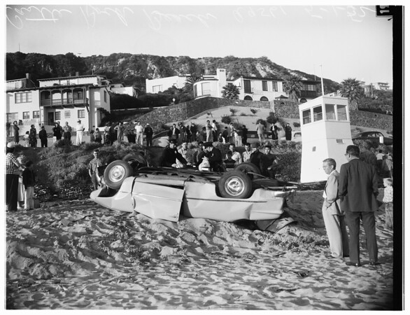 Auto plunges over embankment onto beach, on Pacific Coast highway at Castle Rock, 1952.