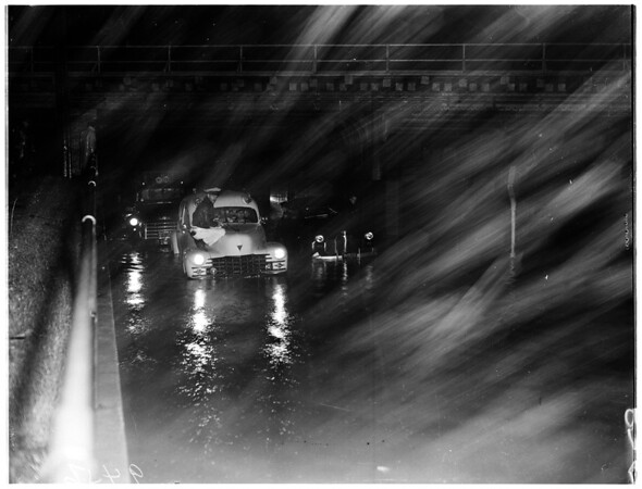 Flooded streets ...Cars and trucks inch along Grande Vista Avenue at Union Pacific Avenue underpass, 1952