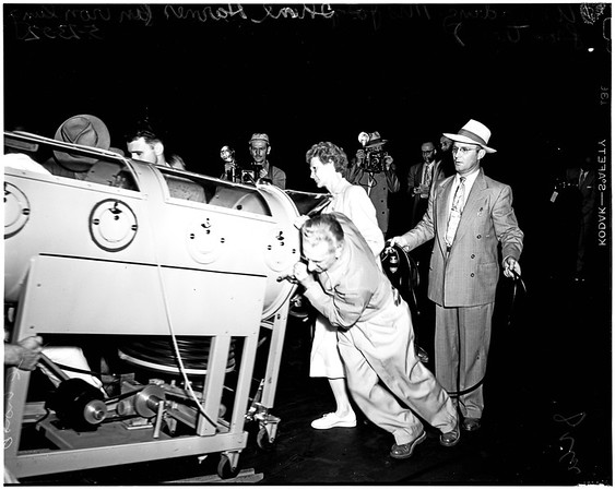 Iron lung patient unloaded from train (Union Terminal), 1952