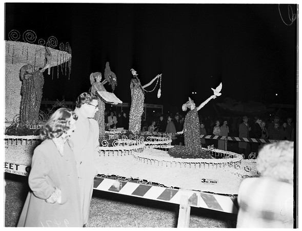 Tournament of Roses floats at night ...General views and closeups of some spectators, 1952