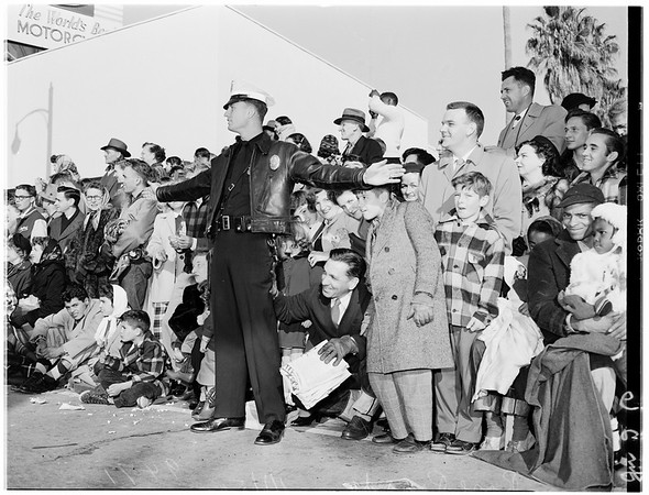 Sidelights of Rose Parade ... Spectators line sidewalks ... Ambulance ... Casualty being carried on stretcher ... Group keeps warm at small street bonfire...Crowd around heart attack victim, 1952