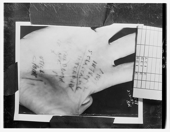 Bookie writes on palm of his hand, 1952
