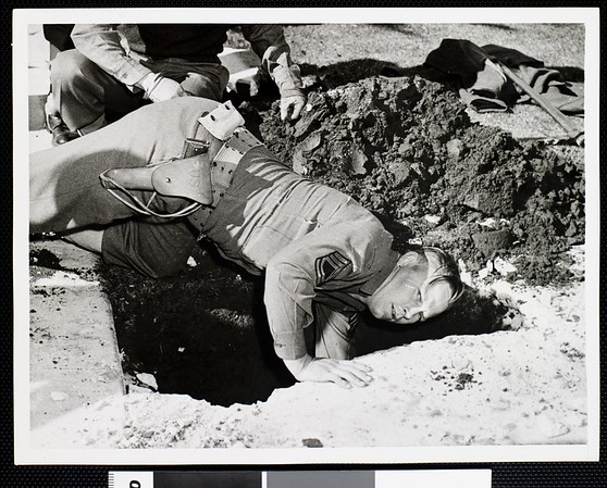 Sergeant C.M. Weathers digging out an unexploded anti-aircraft shell, 1942