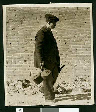 Aged Chinese taking his belongings from quarters in one of structures to be torn down, 1933