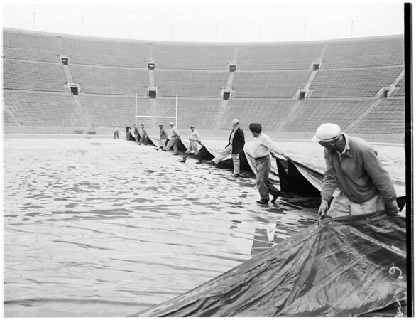 Canvas over field at Los Angeles Memorial Coliseum to preserve for USC vs UCLA grid game, 1955