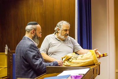 Synagogue leader Ken Wolf and Shmuel Bowman examine Torah Scroll