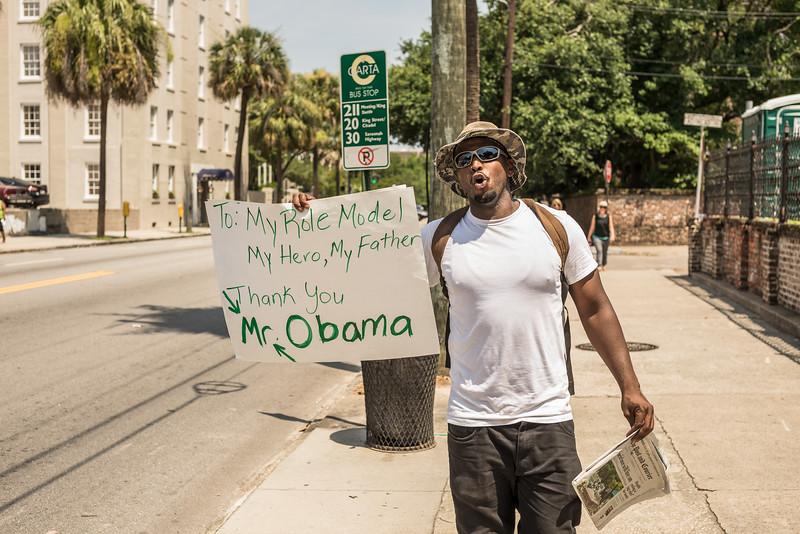Terrance Alamor, of Charleston, holds a sign on the Meeting Street sidewalk. Friday, June 26, 2015