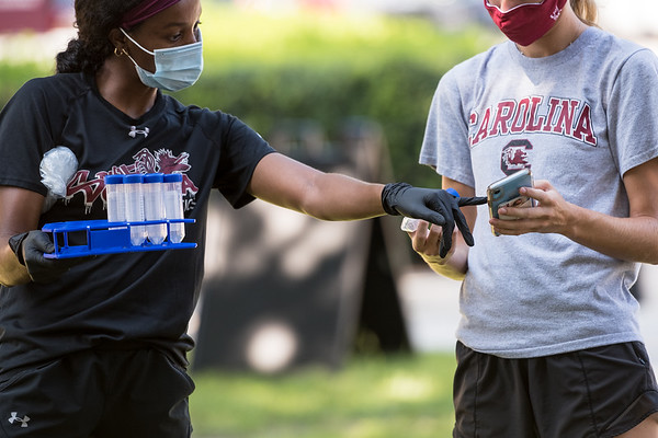 A volunteer hands a student at The South Carolina University a vial to collect saliva for a COVID-19 test on Davis Field outside of Thomas Cooper Library on Sept. 2, 2020. John A. Carlos II/ Special to The Post and Courier