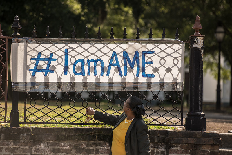 Melvina Lewis, stares at #IamAME sign.