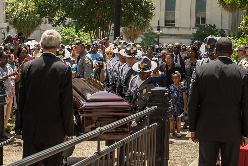 Senator Pinckney's youngest daughter looks on as her fathers casket makes it way into the State House.