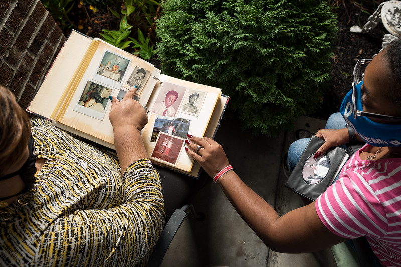 Shayla and Martha Jones, look at family photos and share their memories of Shirley and Demetria Banister. John A. Carlos II / Special to The Post and Courier