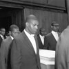 Malcolm X and pallbearers carrying casket at funeral of Ronald Stokes, 1962