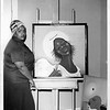 Folk artist Varnette P. Honeywood with two of her paintings, after 1970