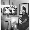 Folk artist Varnette P. Honeywood with three of her paintings, after 1970