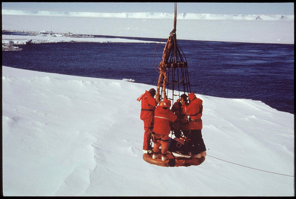 Scientists being transported by crane between the ship and the ice in the Antarctic, 1999