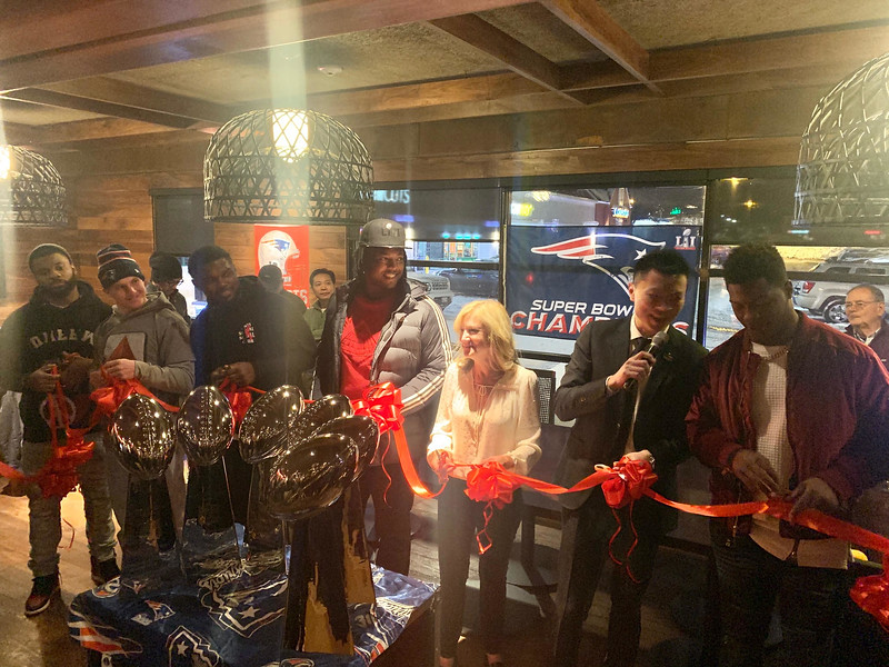Karma owner Iverson Guo of Quincy cuts the ribbon with Town Manager Jodi Ross and several Patriots.