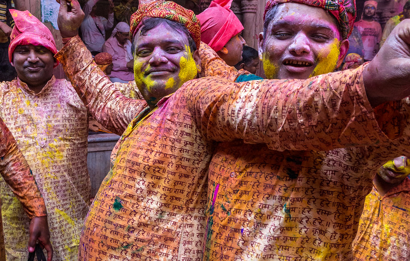 "These Indian devotees of Lord Krishna likely came to ""play Holi"" in this particular Vrindavan temple because of its close association with Krishna. The writing on their shirts is the Hare Krishna mantra."