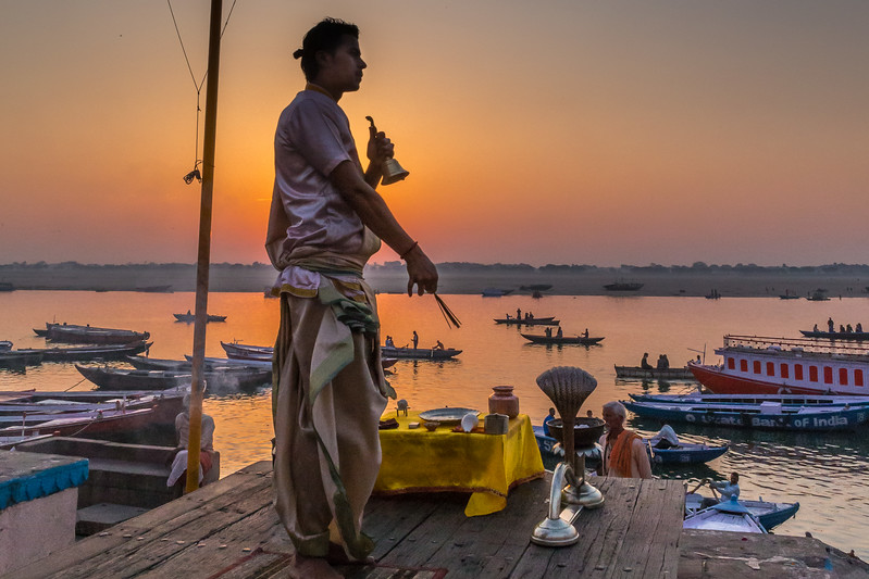 Along the shores of the Ganges River in Varanasi, a Hindu guru greets the rising sun with ceremony.