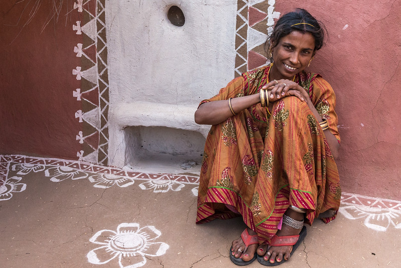This woman welcomes visitors into the beautifully painted courtyard of her home in the Thar desert of Rajasthan, India