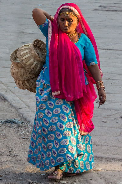 A basket maker crosses a Jodhpur square in the late afternoon sun, returning home with her unsold baskets.