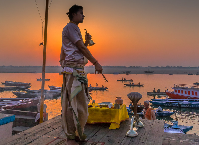 A sadhu greets the sunrise over the Ganga in Varanasi with ceremony.