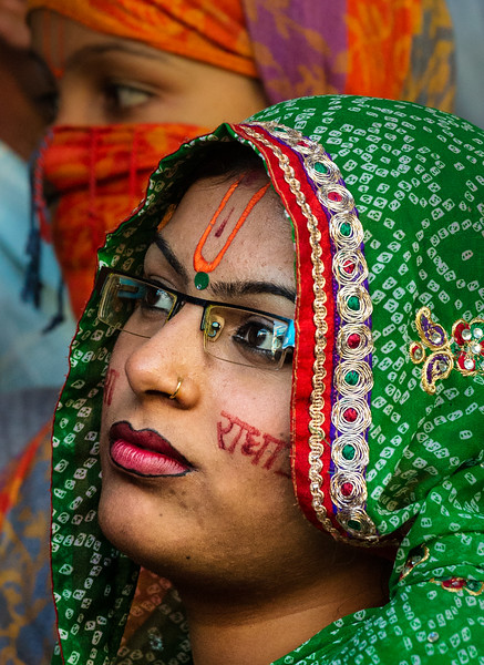 Outside a Hindu temple, this Holi celebrant awaits entrance. The writing on her cheek honors Lord Krishna.