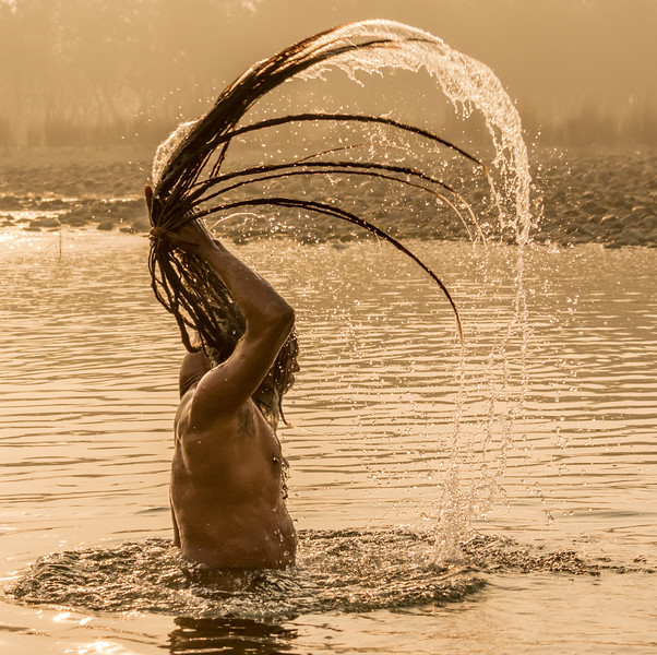 Some sadhus keep their hair very long, and ordinarily wrapped into a bun. That long hair  can add drama to a sunrise bath in the Ganga.