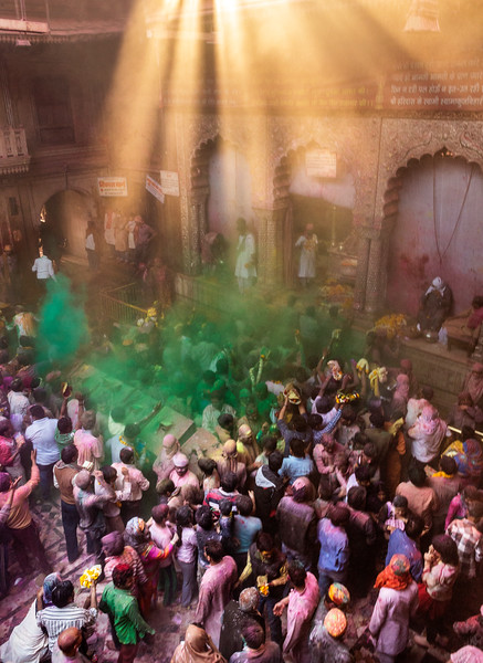 Inside a Hindu temple, clouds of green powder linger in the air and other colors decorate celebrants and surfaces, as well.