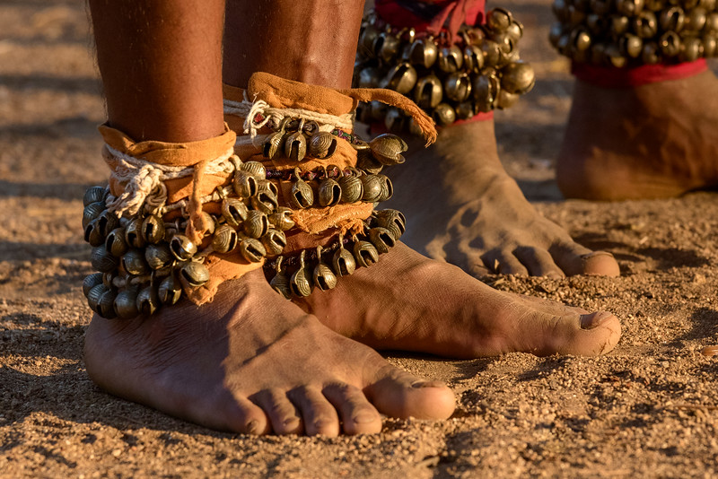 The feet of these Gond women dancers are adorned with ghungroos (strings of small bells) to accentuate the rhythmic aspects of their foot movements. Indian dances often emphasize foot movements to symbolize the connection a dancer makes with Mother Earth.