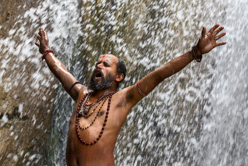 A sadhu revels in the cleansing water of a mountain waterfall in a Ganga tributary stream near Rishikesh.