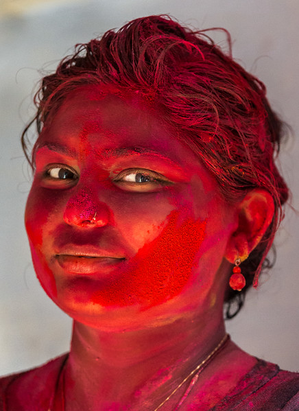 Vrindavan, India. This proud Holi celebrant is covered in red paint. As lines of celebrants pass each other entering and exiting the temple, people headed in one direction gently apply paint or colored power to the people heading in the other direction.