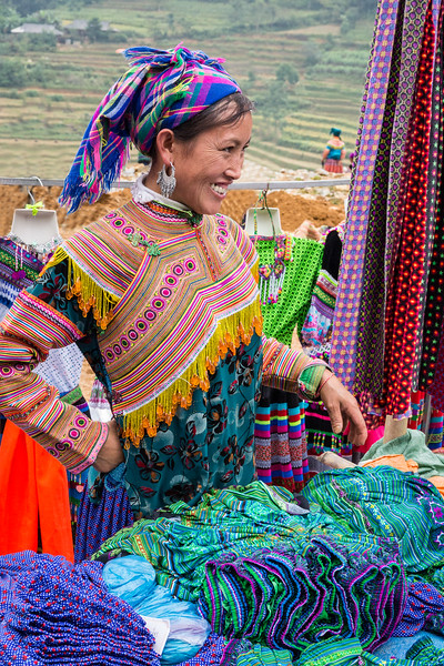 Sapa, Vietnam. A Flower Hmong clothing vendor, with northern Vietnam terraced rice fields in the background. Flower Hmong are among the most colorfully dressed of Vietnam's minority hill tribes.