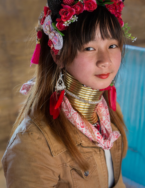 Chiang Rai Province, Thailand. A young woman in a Padaung Karen village market stall. These neck coils press down on the wearer's clavicle and rib cage, resulting in the appearance of a long neck.
